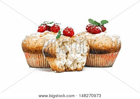 Raspberry muffins decorated with fresh berries and lemon balm leaves isolated over white background