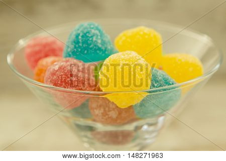 Many jellybeans close up in glass jar with differents colors on wooden background