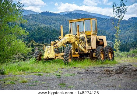 An old yellow grader on mountainous road construction.