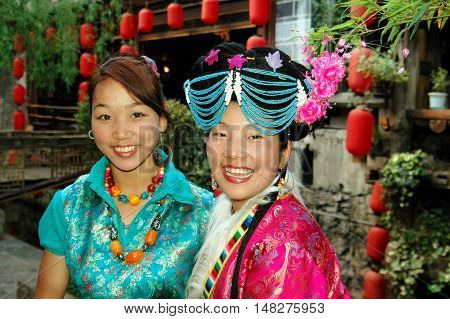 Lijiang China - April 20 2006: Two women workers at a restaurant wearing traditional Naxi clothing and jewelry on Xing Hua Street