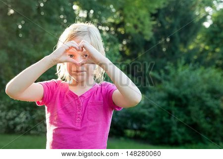 Pretty young girl looking at camera through heart symbol formed by her hands. Warm natural light selective focus and intentional bokeh evoke emotion. Copy space on right side of frame if needed.