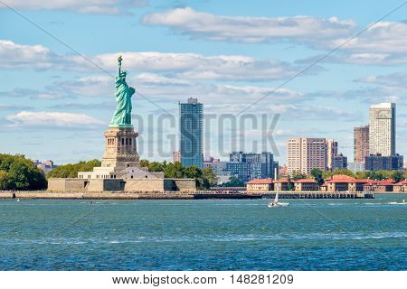 The Statue of Liberty on the New York Harbor with city buildings on the background