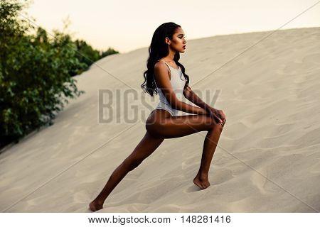 Attractive African-American girl in swimwear on sandy beach