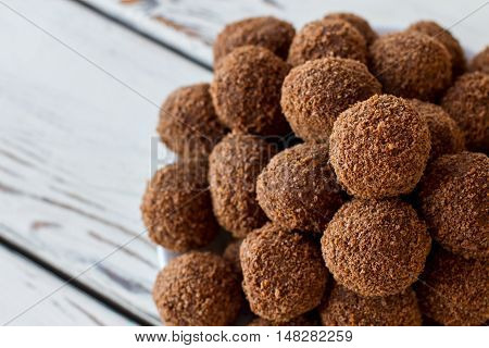 Brown colored sweets. Ball shaped candies with crumbs. Dessert with cocoa powder. Sweet dish high in calories.