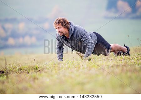 Handsome young runner doing push ups in sunny autumn nature