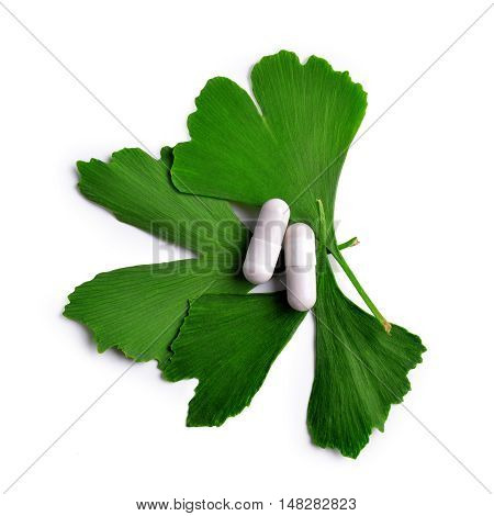 Ginkgo Biloba leaves with capsules isolated on white background