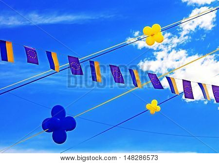 Flags of European Union and Ukraine balloons over blue sky