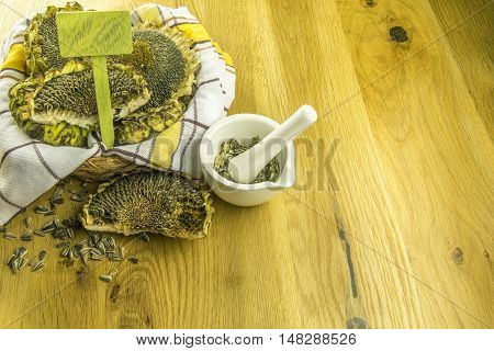 Mortar with crushed sunflower seeds - Basket with sunflower and a white mortar with crushed sunflower seeds on a wooden table