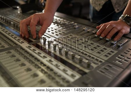 Hands of musician tuning faders of music mixer