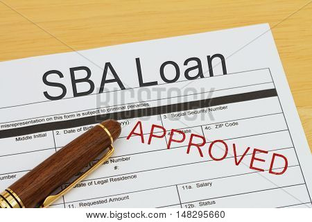 Applying for a SBA Loan Approved SBA Loan application form with a pen on a desk with an approved stamp