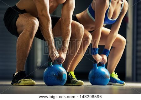 Fit man and woman training by kettle bell.