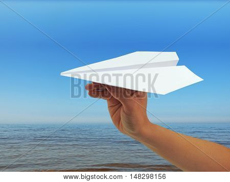 Paper plane in woman hand. Isolated on sky background.