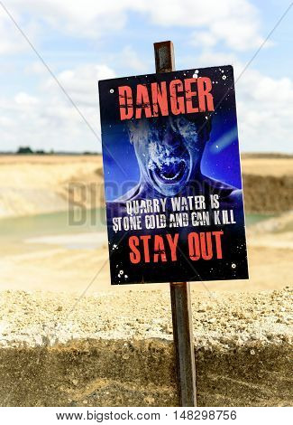 SILVER END, ENGLAND - AUGUST 29, 2016: Cold water kills warning sign at a local quarry showing a man drowning in cold water designed to keep peopple away from the sand pit waters