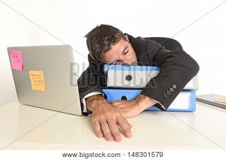young tired and wasted businessman working in stress at office laptop computer looking exhausted and overwhelmed by paperwork heavy load sleeping on folders desk in overwork concept