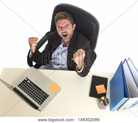 young attractive businessman crazy happy doing fist victory sign sitting at office computer desk celebrating career promotion in business success concept isolated on white background