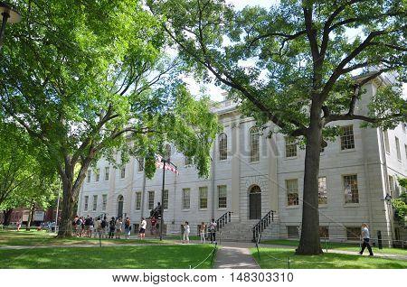BOSTON, USA - AUG 12, 2011: Tourists in front of John Harvard Statue and University Hall on Old Harvard Yard, Harvard University on August 12, 2011 in Cambridge, Boston, Massachusetts, USA.