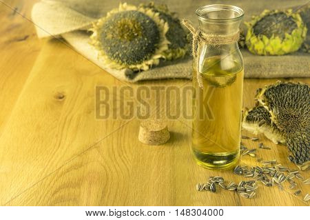 Bottle with sunflower oil in rustic settings - Sunflower oil in a glass bottle on a wooden table and sunflower plants in the background