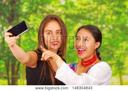 Two beautiful young women standing together facing camera, one wearing traditional andean clothing, the other in casual clothes, holding up mobile posing for selfie smiling, park background.