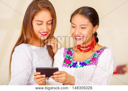 Two beautiful young women posing for camera, one wearing traditional andean clothing, the other in casual clothes, holding mobile between them interacting, both smiling, park background.