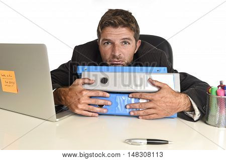young tired and wasted businessman working in stress at office laptop computer looking exhausted and overwhelmed by heavy paperwork load on desk in overwork concept
