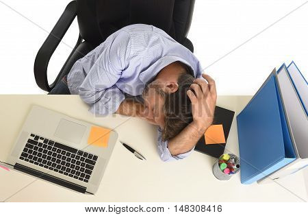 young tired and wasted businessman working in stress at office laptop computer looking exhausted and overwhelmed by heavy work load sleeping on desk in overwork concept