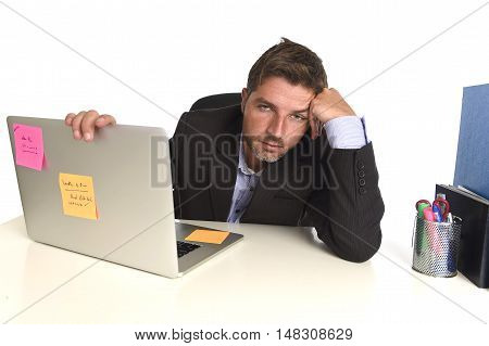 young tired and wasted businessman working in stress at office laptop computer looking exhausted and overwhelmed by heavy work load bored on desk in overwork and overtime concept