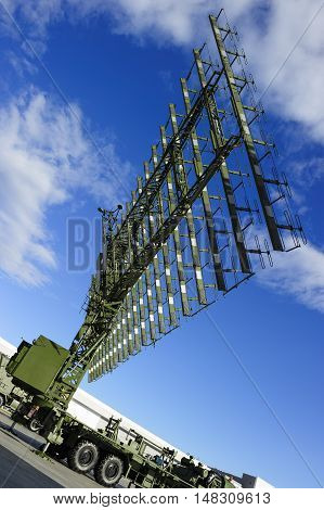 Air defense radar of military mobile antiaircraft system on heavy truck in green color, modern army industry, beautiful clouds and blue sky on background