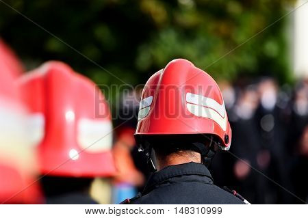Firefighters wearing firefighter helmets are seen from behind during parade