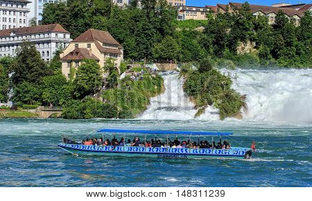 Neuhausen am Rheinfall, Switzerland - 22 June, 2016: people in a boat on the the Rhine river just below the Rhine Falls. The Rhine Falls is the largest plain waterfall in Europe, located on the Rhine river in Switzerland.