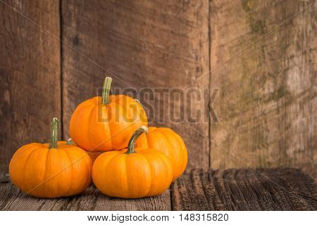 Pumpkins against a rustic weathered wood background.