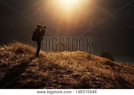 Woman photographer in the mountains on an early autumn mornining