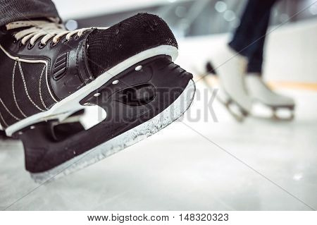 Man's hockey skates and women's figure skates on ice background.