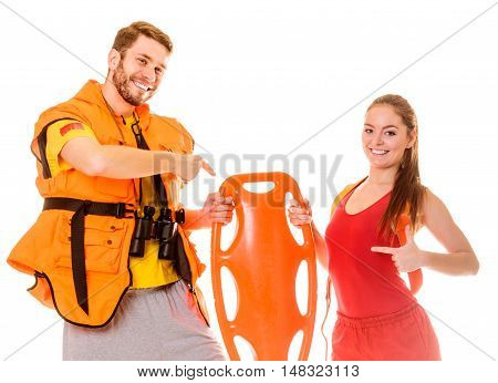 Lifeguards in life vest jacket pointing at rescue tube buoy . Man and woman supervising swimming pool. Accident prevention.