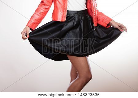 Fashion and style. Part body of mixed race woman wearing stylish red jacket coat and black leather skirt. Fashionable girl posing indoor.