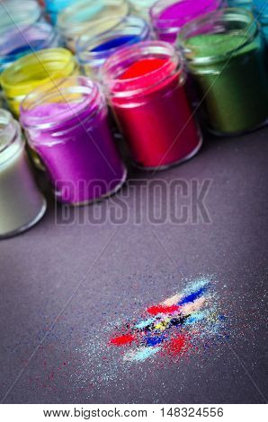 a lot of multicolored paint in jars for makeup artistry