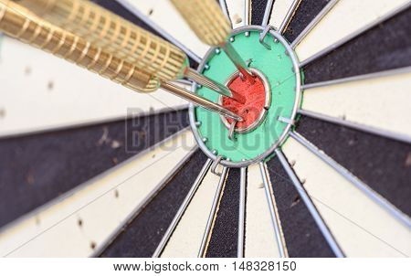 Three Bullseye Darts On A Dart Board