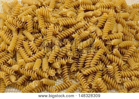 Pile of dry uncooked whole wheat rotini pasta