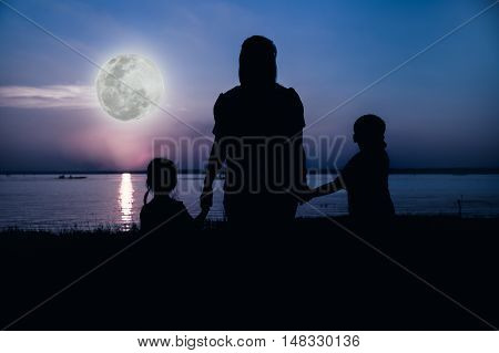 Silhouette of parent and child enjoying the view at riverside. Colorful blue sky and bright full moon background. Friendly family. Cool colors tone photo effect. The moon were NOT furnished by NASA.