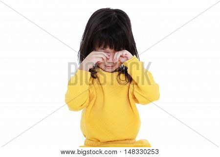 Chinese child waking up girl looks sleepy in the morning isolated on white background. A tired asian girl in pajamas rubbing eyes.