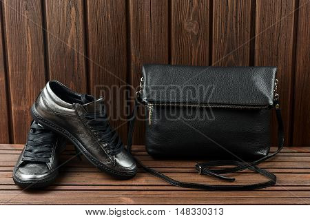 Leather Upper Metallic Womens Shoes And Black Leather Bag On Brown Wooden Background.  Womens Leathe