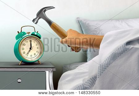Human hand hitting alarm clock with hammer