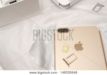 PARIS FRANCE - SEP 16 2016: New Apple iPhone 7 Plus unboxed in the first day of sales - inserting SIM card in new phone. New Apple iPhone acclaims to become the most popular smart phone in the world in 2016