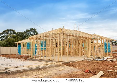 New residential construction home framing against a blue sky. Construction site preparation