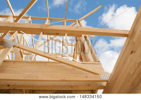 New residential construction home framing against a blue sky.Shallow focus.