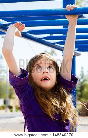 A young girl with a missing front tooth and long brown hair crosses the blue monkey bars at a park playground.