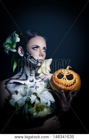Young attractive girl with creative make-up for Halloween. Close-up portrait. Mysterious and frightening image of lilies and red eyes. Witchcraft. Awful. Jack-o'-lantern