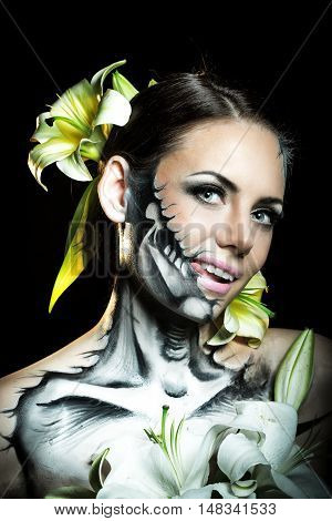 Young attractive girl with creative make-up for Halloween. Mysterious and frightening image of lilies. Witchcraft. Jitters.