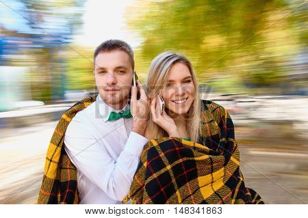 Beautiful young couple taking calls with mobile