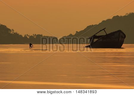 photographer taking a photo of old wreck boat against sun rising sky