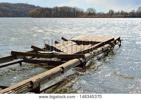 Broken wooden dock in the waves of the river